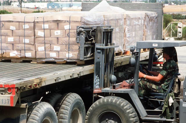A forklift is used to pull a pallet of supplies from the bed of a cargo truck during Exercise GALLANT EAGLE '84