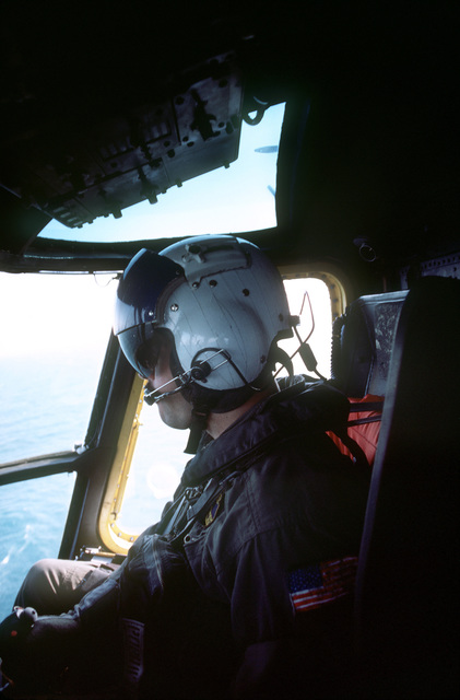 A pilot from Helicopter Mine Countermeasures Squadron 14 (HM-14) sits in the cockpit of an RH-53D Sea Stallion helicopter during Operation INTENSE LOOK