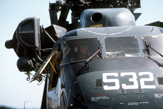 A plane captain mans the brakes of an RH-53D Sea Stallion helicopter as it is maneuvered into a parking space aboard the amphibious transport dock USS SHREVEPORT (LPD 12) during Operation INTENSE LOOK