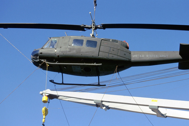 A UH-1 Iroquois helicopter is offloaded from the vehicle cargo ship USNS CAPELLA (T-AKR 293). The aircraft will be used in support of Exercise GALLANT EAGLE '84