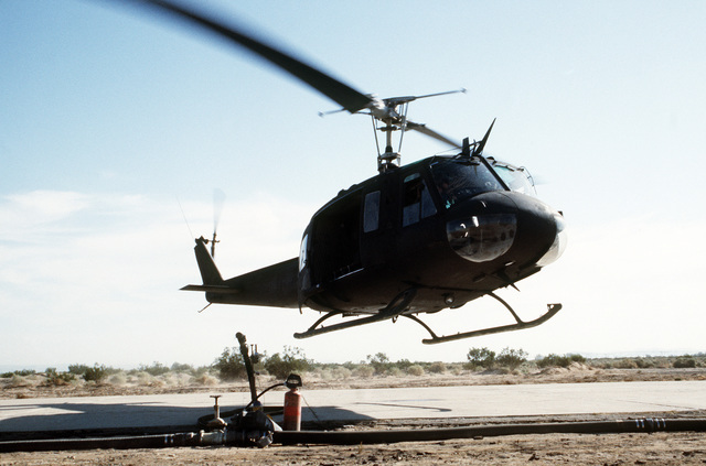 A UH-1 Iroquois helicopter lands at a fuel depot for refueling during Exercise GALLANT EAGLE '84