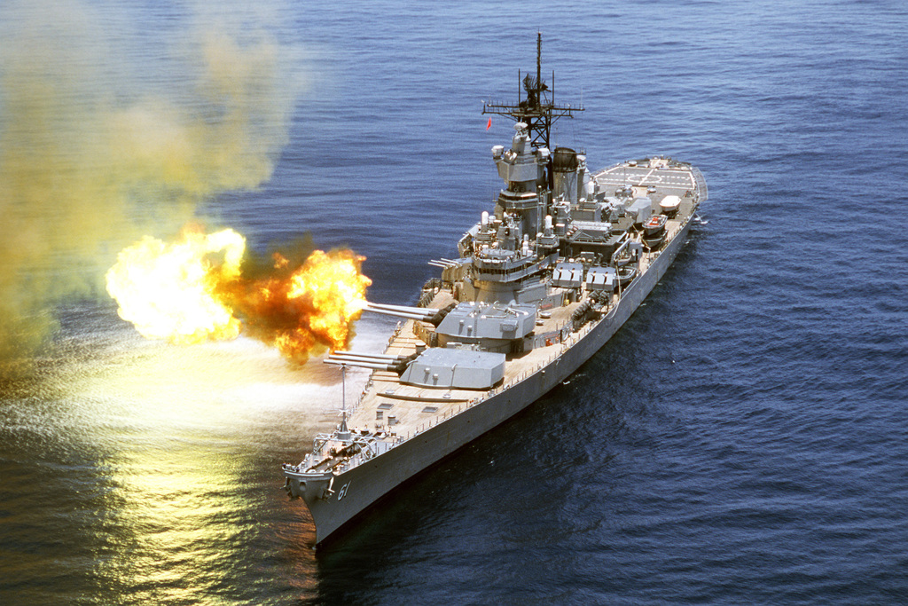 An aerial port bow view of the battleship USS IOWA (BB 61) firing its No. 2 turret 16-inch 50-cal. guns off the starboard side