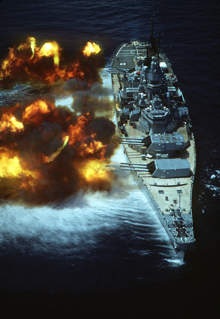 """An aerial starboard bow view of the battleship USS IOWA (BB-61) as a """"firepower"""" demonstration is conducted for embarked dignitaries from Guatemala. Notice the 16-inch guns in various stages of recoil"""