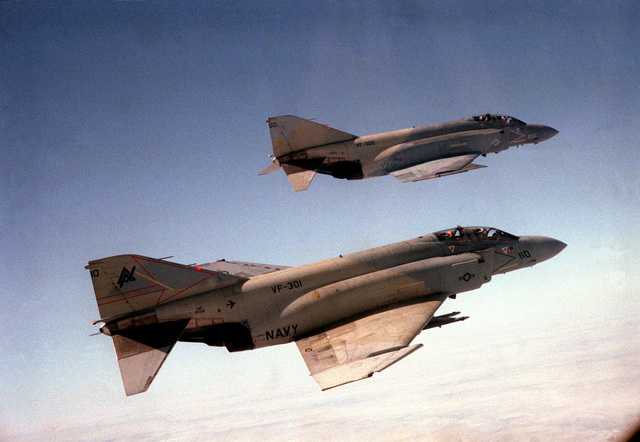 An air-to-air right side view of two F-4S Phantom II aircraft. They are assigned to Fighter Squadrons 301 and 302 (VF-301, 302)
