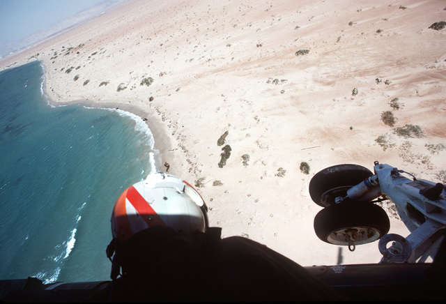 An aircrewman from Helicopter Mine Countermeasures Squadron 14 (HM-14) look down on the coastline from an RH-53D Sea Stallion helicopter during Operation INTENSE LOOK