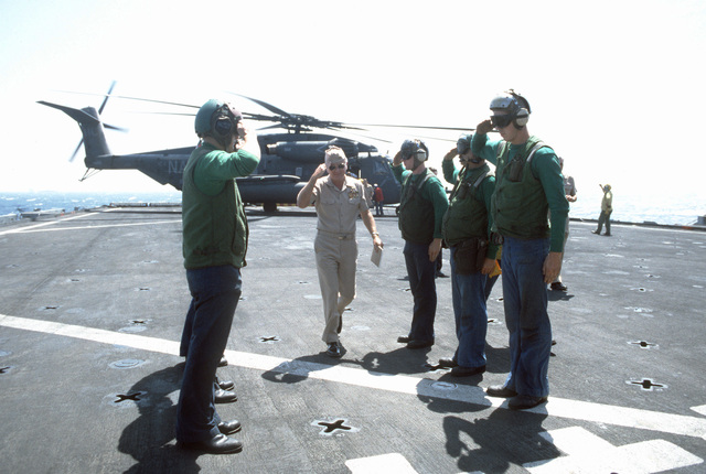 Flight deck crewmen aboard the amphibious transport dock USS SHREVEPORT (LPD 12) salute Commodore Alvin S. Newman, commander, US Naval Forces Central Command, as he exits a CH-53E Sea Stallion helicopter during Operation INTENSE LOOK