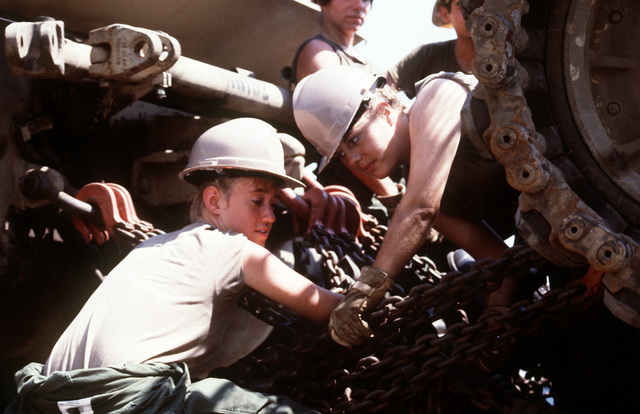 PFC. Laura Allen, right, and PVT. 2 Patricia Cotter secure an M-60A1 main battle tank to a flatbed rail car, after it was offloaded from the vehicle cargo ship USNS CAPELLA (T-AKR 293) during exercise Gallant Eagle '84. The women are from the 567th Transportation Battalion