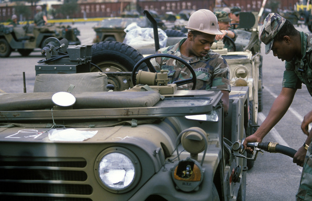 Private First Class (PFC) Garfield Jones refuels an M151 lightweight vehicle as Sergeant (SGT) B. Jiles looks on from the driver's seat, during Exercise GALLANT EAGLE '84 at the National Training Center