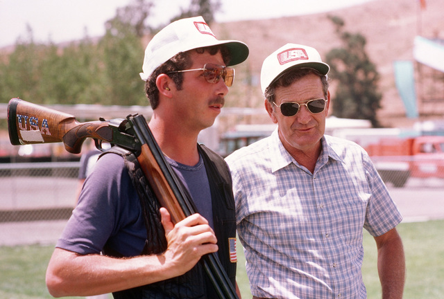 Retired Army MASTER Sergeant Burl Branham, right, from Fort Benning, Georgia, is the team shotgun coach in the shooting competition at the 1984 Summer Olympics. Standing with him is team member STAFF Sergeant Matthew A. Dryke, who won a gold medal for his performace in the skeet shooting event