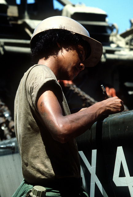 SPEC. 4 Anita Sledge, 870th Transportation Company, checks a vehicle identification number during exercise Gallant Eagle '84 at the National Training Center