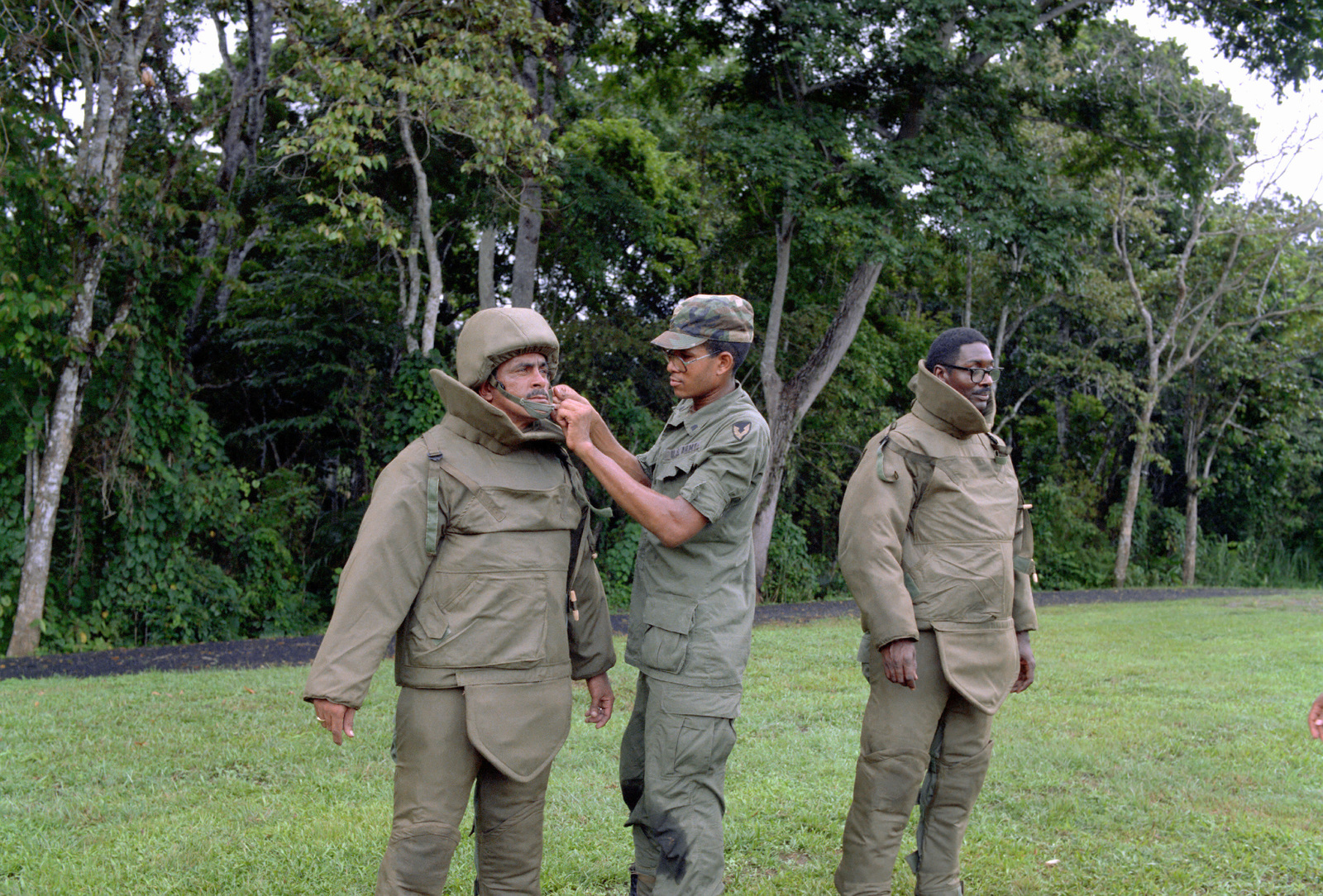 SPECIALIST Fourth Class Brown assists Sergeant First Class Matilde Almendarez in donning body armor to be used by explosive ordnance disposal units to test its effectiveness after eight months of storage in the tropics. STAFF Sergeant Milus Reeves is also wearing the two-piece suit which is constructed of Kevlar and Nomex fabrics