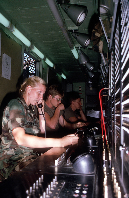 SPECIALIST Fourth Class (SPC) Devora Probeck, left, Private First Class (PFC) Tim Chier, center, and PFC Harry Dobbs work inside an MTC-9 switchboard van during Exercise GALLANT EAGLE '84