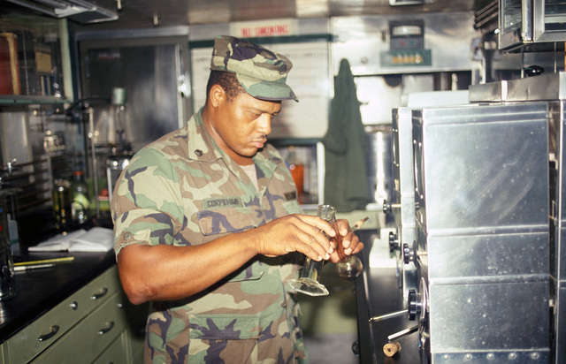 STAFF Sergeant (SSG) Corpening, 23rd Lab Detachment, tests fuel for contamination during Exercise GALLANT EAGLE '84 at the National Training Center