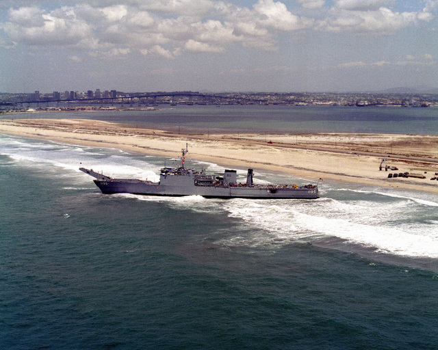 An aerial port beam view of the tank landing ship USS BARBOUR COUNTY (LST 1195) after running aground on Silver Strand