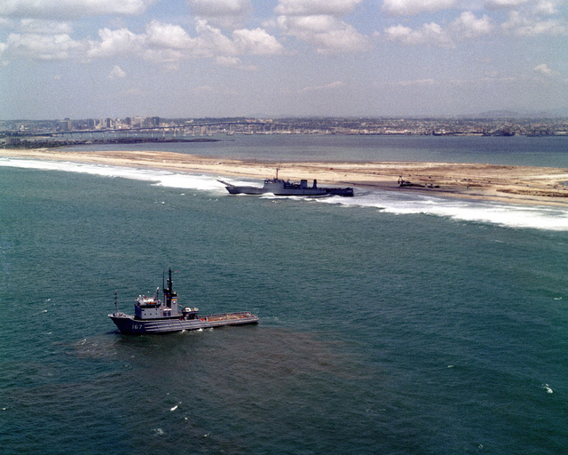 An aerial port bow view of the fleet tug USNS NARRAGANSETT (T-ATF 167) preparing to assist the tank landing ship USS BARBOUR COUNTY (LST 1195) after running aground on Silver Strand