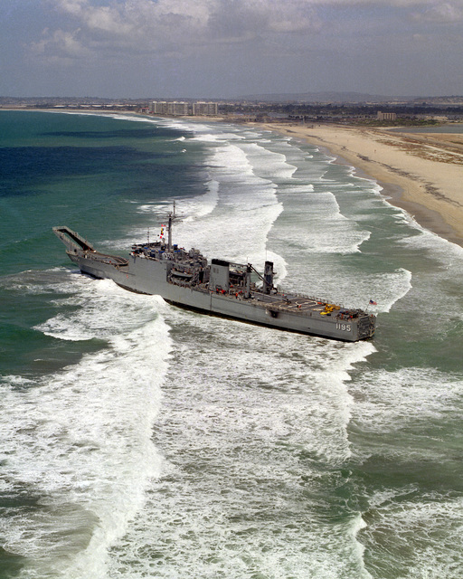 An aerial port quarter view of the tank landing ship USS BARBOUR COUNTY (LST-1195) after running aground on Silver Strand
