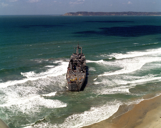 An aerial stern view of the tank landing ship USS BARBOUR COUNTY (LST 1195) after running aground on Silver Strand