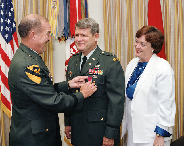 Major General (MGEN) Burton D. Patrick, CHIEF of Legislative Liason, Headquarters, Department of the Army, presents the Legion of Merit to Colonel (COL) Cornelius C. Holcomb, Deputy to the CHIEF of Plans and Operations Division, Office of the CHIEF of Legislative Liason. Observing the presentation is COL Holcomb's wife, Mary Ellen. The ceremony is taking place at the Pentagon