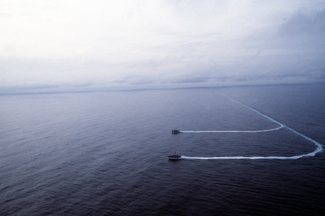 Aerial port beam view of the patrol combatant-missile (hydrofoils) USS HERCULES (PHM 2), foreground, and USS ARIES (PHM 5) underway. The hydrofoils are operating as part of Commander Task Group 28.1.1