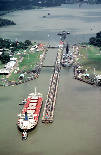 Aerial stern view of the battleship USS IOWA (BB 61) entering the Pedro Miguel Locks during its transit of the canal. The bulk ship Pacific Prestige, out of Hong Kong, enters the locks behind the IOWA