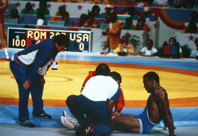 Marine Corps Sergeant Greg Gibson is checked by medical personnel between rounds during a Greco-Roman wrestling match at the 1984 Summer Olympics