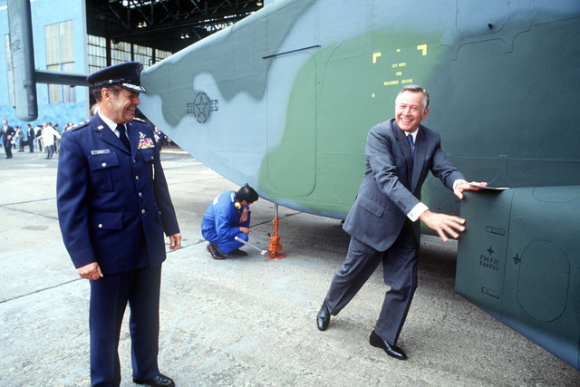 Charles H. Price II, US ambassador to the Court of St. James, assists in the rollout of the first C-23A Sherpa aircraft to be accepted by the US Air Force. Standing by is Lieutenant General Carl H. Cahey, vice commander in chief, US Air Force Europe