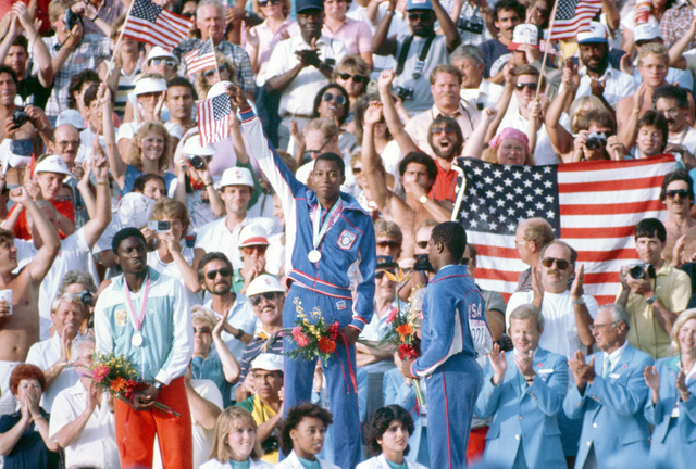 Second Lieutenant Alonzo Babers, US Air Force, waves an American flag from the victory platform after receiving the gold medal for winning the 400 meter race at the 1984 Summer Olympics. Babers is flanked by silver medalist Gabriel Tiacoh, left, of the Ivory Coast and bronze medalist Antonio McKay, right, of Atlanta, Georgia