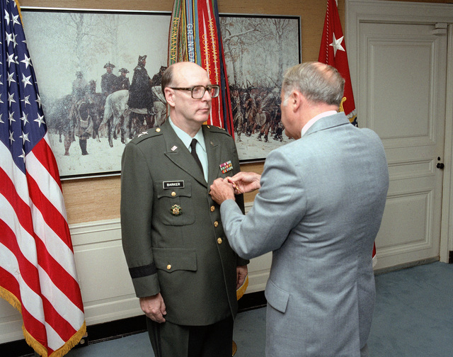 Secretary of the Army, the Honorable John O. Marsh, Jr., presents the Distinguished Service Medal to Major General (MGEN) Llyle J. Barker, Jr., upon his retirement from active duty. The ceremony is being held at the Pentagon