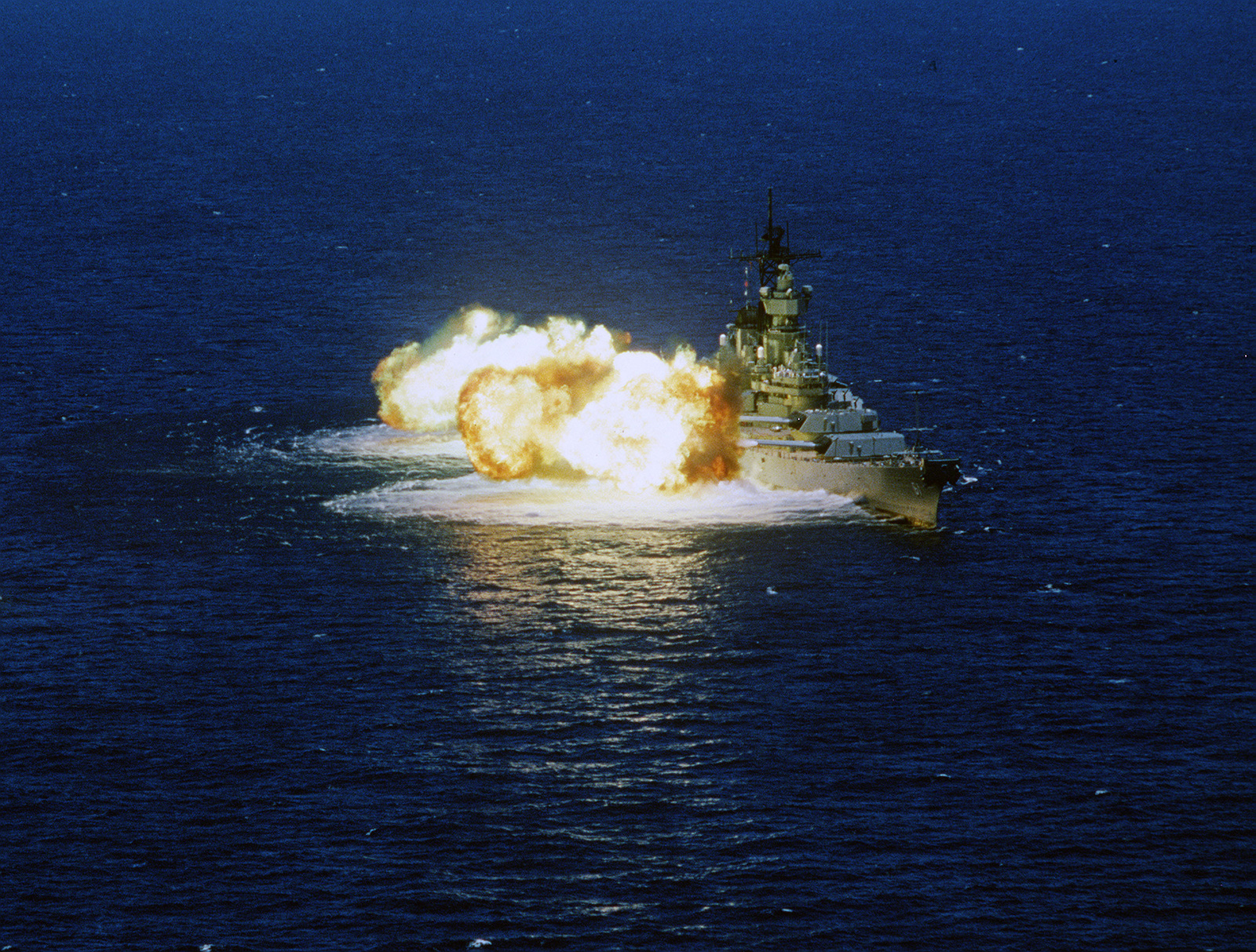 Aerial starboard bow view of the battleship USS IOWA (BB 61) firing a 15 gun salvo to starboard. The 15 gun salvo is comprised of all nine 16-inch .50 caliber main battery guns and the six starboard 5-inch .38 caliber guns. The IOWA is off the coast of Central America