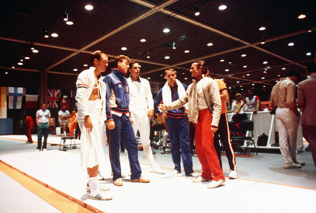 Army First Lieutenant John Moreau, with a towel around his neck, stands with fellow members of the fencing team during the 1984 Summer Olympics