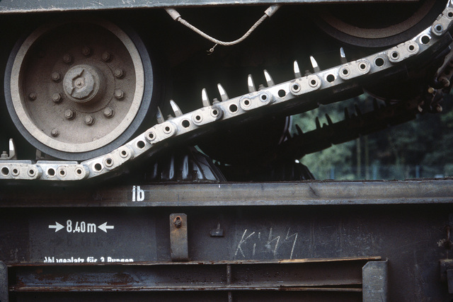 A metal chock is used to help secure an M1 Abrams main battle tank to a rail car. The tank will be used during SPEARPOINT '84, a phase of Exercise REFORGER '84