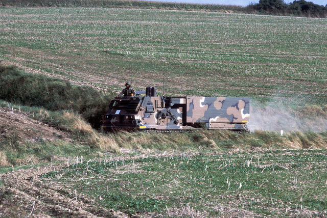 An M270 227 mm multiple launch rocket system from B Battery, 1ST Battalion, 92nd Field Artillery, is deployed on a dry-fire mission during SPEARPOINT '84, a phase of Exercise REFORGER '84