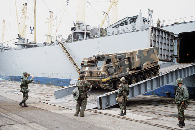 An M270 227 mm multiple launch rocket system vehicle is offloaded from the vehicle cargo ship SS ADMIRAL WILLIAM M. CALLAGHAN. The launcher will be used in SPEARPOINT '84, a phase of Exercise REFORGER '84