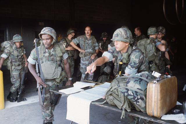 An officer of Headquarters and Headquarters Company, 1ST Tiger Brigade, 2nd Armored Division, calls out names from a flight roster prior to the departure of the 44th Chemical Company to West Germany for SPEARPOINT '84, a phase of Exercise REFORGER '84