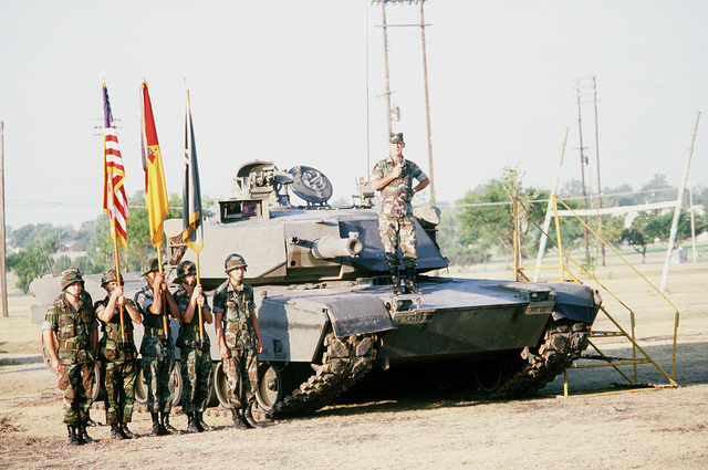 Colonel (COL) Benjamin W. Covington III, commander, 1ST Tiger Brigade, 2nd Armored Division, speaks to his troops while standing on an M1 Abrams main battle tank. The brigade is preparing for deployment to West Germany for SPEARPOINT '84, a phase of Exercise REFORGER '84. An Army color guard stands at attention