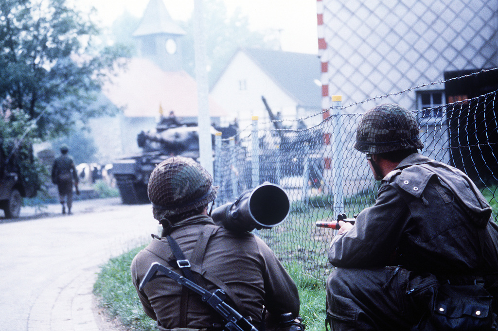 Dutch soldiers armed with Uzi submachine guns and an 84mm M-2 Carl Gustaf recoilless gun observe a convoy of tanks rolling through a village. The soldiers are participating in Spearpoint '84, a phase of Exercise Reforger '84
