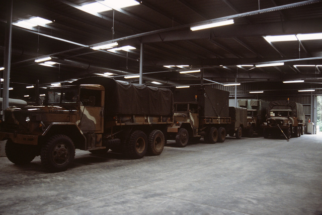 M35A2 2 1/2 ton trucks are stored in a warehouse at a prepositioning of materiel configured to unit sets (POMCUS) site prior to fueling, battery installation and safety checks during SPEARPOINT '84, a phase of Exercise REFORGER '84