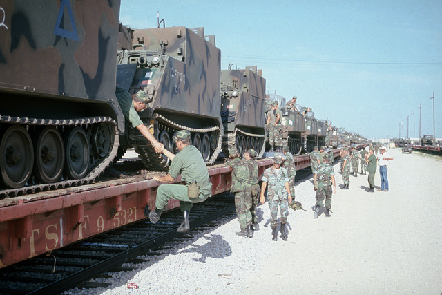 Soldiers complete tie-down procedures for armored vehicles loaded on rail cars. The vehicles will be transported by rail to Beaumont, Texas, where they will be shipped to West Germany for SPEARPOINT '84, a phase of Exercise REFORGER '84