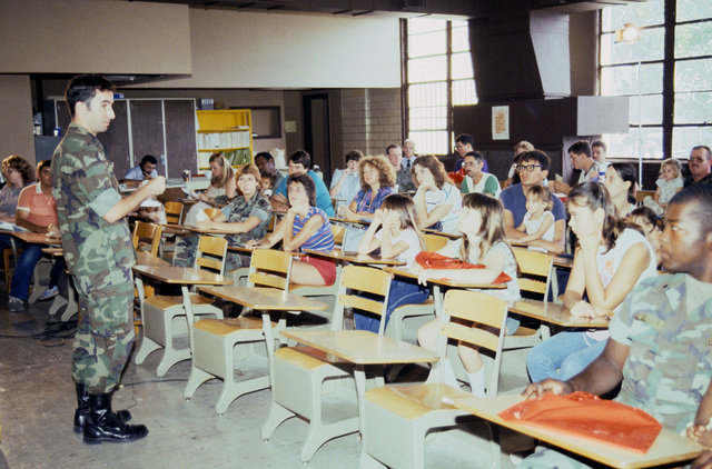 The commander of Headquarters and Headquarters Co., 1ST Brigade, 2nd Armored Division, conducts the Reforger Family Day briefing for families of soldiers deploying to West Germany for SPEARPOINT '84, a phase of Exercise REFORGER '84