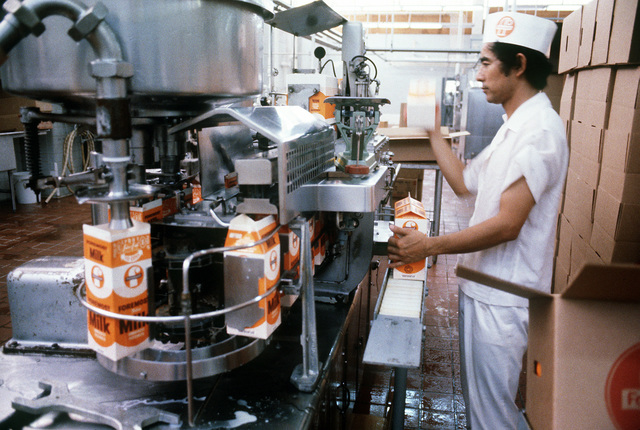 A civilian workman closes milk cartons at the Foremost dairy. The dairy holds a contract to supply milk to Kadena Air Base and other area military facilities