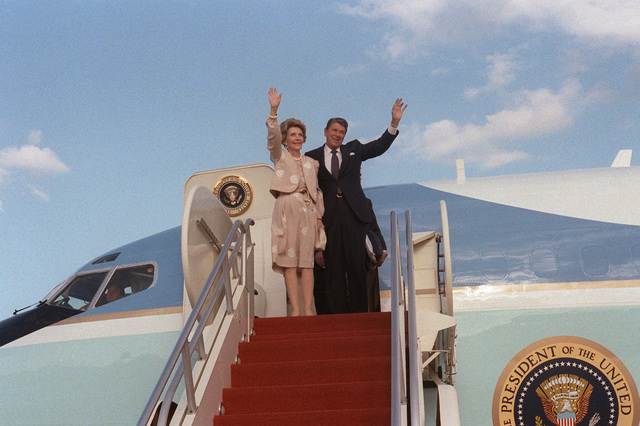 President and Mrs. Reagan wave at the awaiting crowd as they return from a recent trip