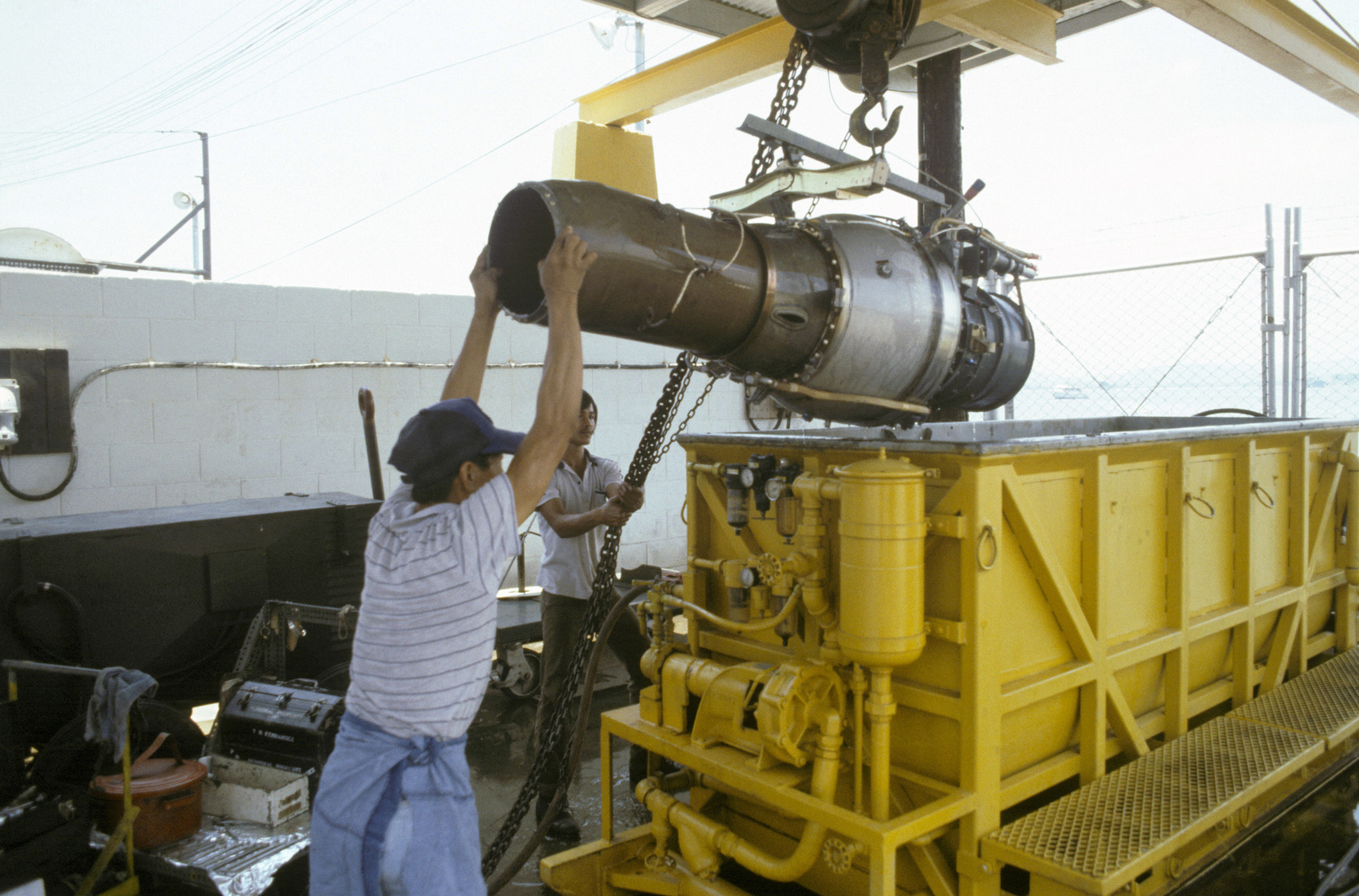 Teledyne Ryan technicians hoist the engine of a BQM-34