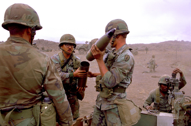 Members of B Battery, 7th Bn., 8th Field Artillery Regiment, 25th Inf. Div., prepare a 105mm shell for firing from an M-102 howitzer during a live-fire exercise at the Pohakuloa Training Area