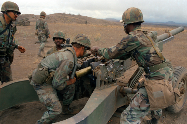 Members of Battery B, 7th Battalion, 8th Field Artillery Regiment, 25th Infantry Division, load a 105 mm M102 Howitzer during a live-fire exercise at the Pohakuloa Training Area
