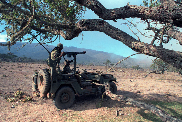 Members of the 1ST Scout Platoon, 19th Infantry, aboard an M151 jeep wih an M60 machine gun mount, search for opposing forces near Lava Ridge during Exercise OPPORTUNE JOURNEY 4-84