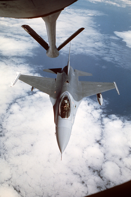 An F-16 Fighting Falcon aircraft from the 388th Tactical Fighter Wing approaches a tanker aircraft for in-flight refueling. Note that the aircraft is armed with a AIM-9 Sidewinder air-to-air missile on its right wing tip. The F-16 is en route to Norway for use during Exercise CORNET COLT