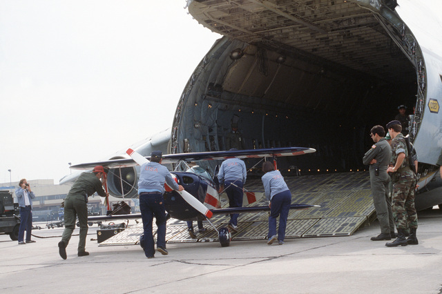 A biplane, one of nine stunt planes, is loaded onto a C-5A Galaxy transport aircraft belonging to Military Airlift Command for transportation back to the United States. The planes belong to the US World Aerobatic Champion Team and were used competitively in the 12th World Aerobatic Championships at Bekescsaba, Hungary