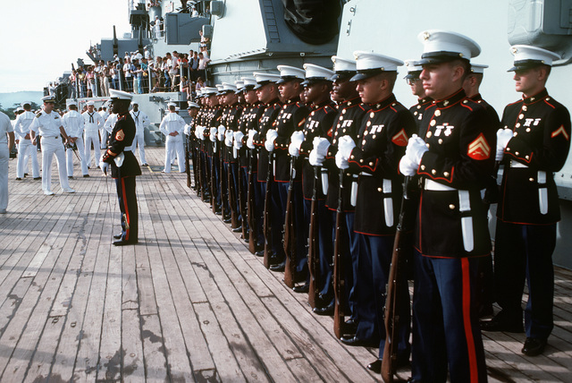 Members of the Marine detachment aboard the battleship USS IOWA (BB-61) stand at the ceremonial at ease position prior to a visit by the ambassador to Panama, Everett E. Briggs