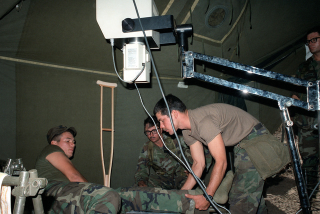 SPC5 Eric L. Zamora, a medic with the 25th Inf. Div., prepares to x-ray the leg of PVT Felix Gonzalez during an exercise at the Pohakuloa Training Area. Looking on is CPT Leif G. Johnson, commander of Company C