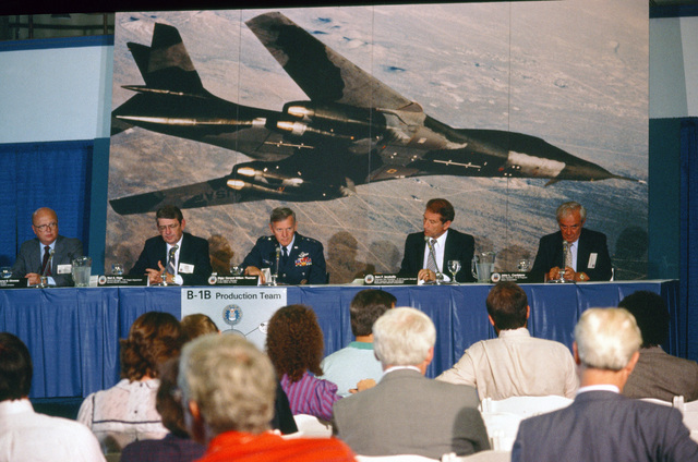 Attending a news conference during the rollout of the first production model B-1B aircraft are, from left to right: Gerald Gimness, B-1B program manager, Boeing Military Airplane Co.; Ned A. Hope, general manager, F101 Project Department, General Electric Co.; Major General (MGEN) William Thurman, B-1B program manager, Wright-Patterson Air Force Base; Sam F. Iacobellis, executive vice president, Rockwell International; and John L. Canfalone, vice president, B-1B program, Eaton Corp